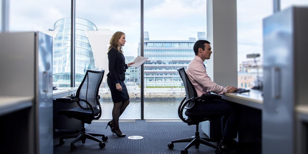 Business woman walking towards man at desk